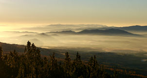 Morning fog beneath the mountains Stock Photography