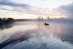 Morning fog boat lake. Morning nature scene (landscape): sky, clouds and fog (mist) and lonely fishing boat with fisher reflected on the water surface (lake stock image