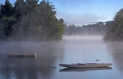 Morning Fog on a Lake. Early morning fog on a lake. A boat and dock are in the foreground Royalty Free Stock Image