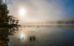 Sunrise through morning fog on the lake. Royalty Free Stock Images