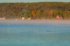 Morning fog lifts on a calm lake to reveal countryside colors in early autumn at Silver Lake, Castile, NY. Fog and frost creates a muted color palette at dawn on Stock Photo