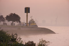 Morning fog at river with ships and industry. Ships at the riverside in morning fog with industrial bakground and pink sunrise Royalty Free Stock Image