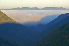 Morning fog at sunrise in autumn mountains of West Virginia in Babcock State Park Royalty Free Stock Image