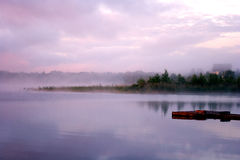 Morning fog water. Morning nature scene (landscape): fog (mist) reflected in the water surface along with reeds, pink and blue sky, trees and a home on the shore Royalty Free Stock Image