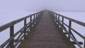 Morning fog on wooden bridge and one walking schoolboy