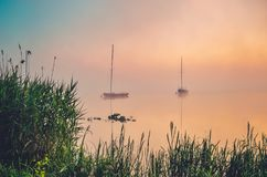 Morning foggy lake landscape. Boats on the lake royalty free stock photography