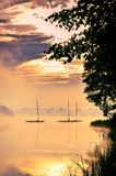 Morning foggy lake landscape. Boats on the lake at sunrise royalty free stock photos