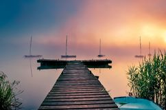 Morning foggy lake landscape. Wooden pier and boats on the lake royalty free stock photos
