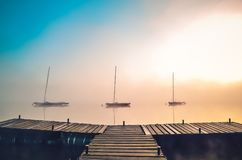 Morning foggy lake landscape. Wooden pier and boats on the lake stock photography