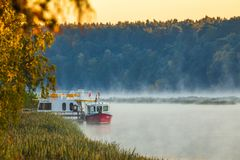 Morning foggy landscape of boats in Nemunas river royalty free stock image
