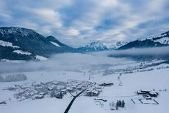 Morning foggy top aerial panoramic view of snow and village with trees and road on the winter landscape background of austrian royalty free stock images