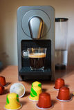 Morning fragrant coffee with capsules. Morning fragrant cup of coffee on the wooden table with colorfull capsules of nespresso Royalty Free Stock Photos