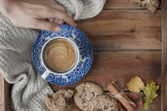 Morning fragrant coffee in a female hand and a wooden background. Biscuit biscuits with chocolate for breakfast and a warm knitted royalty free stock photography
