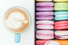 Morning fresh french macaron cookies and blue cup of cappuccino on white table Royalty Free Stock Photos