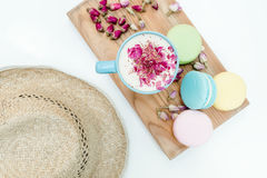 Morning fresh and tasty macarons, cappuccino and roses petal with straw hat on table. Top view Stock Images