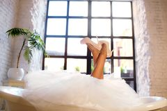 The bride lies in the bathroom, lifted her legs to the top, beautiful slender legs of the bride against the window stock photos