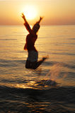 Morning girl. A girl jumps at-sea on a sunrise Royalty Free Stock Photos