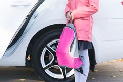 In the morning a girl is standing at the car with a bag for textbooks before going to school stock photos