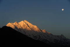 Morning Glow & Full Moon. Rakaposhi (7,788m) in Karakoram mountains. Seen from Duikar village, Hunza Valley, Pakistan Stock Images