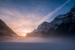Morning Glow in Swiss Alps. Awaiting the sun to rise on a frozen lake in winter in the swiss alps royalty free stock photography