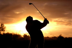 Morning golf. A left handed golfer practices early morning with a beautiful sunrise Stock Photos