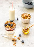 Morning granola in glass with yogurt, honey and milk on white desk Royalty Free Stock Images