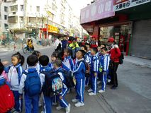 Chinese pupils carry out activities outside school and are on the way. In the morning, a group of pupils carry out activities outside the school and are on the Stock Images