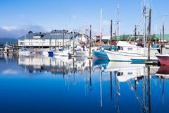 Morning harbor scene, private boats on calm water. Calm morning landscape of harbor piers brimming with fishing boats, Ketchikan, Alaska, USA stock image
