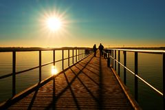 Morning in harbor. Tourists walk on pier above sea. Clear blue sky, smooth water level. Morning in harbor. Tourists walk on pier construction above sea. Sunny royalty free stock photo
