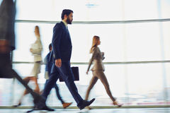 Morning haste. Crowd of modern business people walking down corridor Royalty Free Stock Photos
