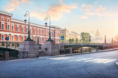 Morning haze on the Moika. Kisses Bridge and St. Isaac`s Cathedral in the sunlight of St. Petersburg Stock Photos