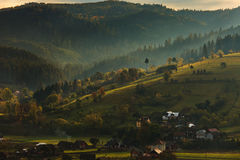 Morning hill with sun and forest. Sunrise in a village, Romania Stock Photo