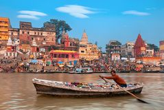 Morning at holy ghats of Varanasi, India. A view of  holy ghats of Varanasi with a boatman sailing Royalty Free Stock Photography