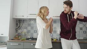 Morning at home happy young couple newly wed dancing listening to music in kitchen stock footage