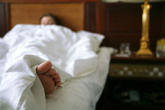 Morning in hotel room. Woman sleeping in a hotel room, selective focus on bare foot Stock Photo