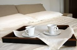 Morning in a hotel room. Two coffee cups on a bed in hotel room royalty free stock images