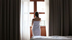 Morning at the hotel. young girl in Bathrobe opens a door to balcony. Full HD. 1920x1080. Morning in the hotel: young female open curtains stock video