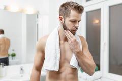 Morning hygiene, Man in the bathroom looking in mirror. Morning hygiene, Handsome man in the bathroom looking in mirror Royalty Free Stock Photo