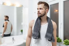 Morning hygiene, Man in the bathroom looking in mirror. Morning hygiene, Handsome man in the bathroom looking in mirror Stock Image