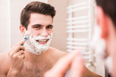 Morning hygiene. Handsome young man is shaving his face and looking at the mirror Stock Photography
