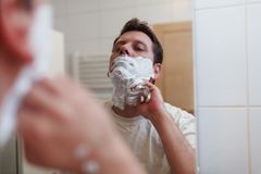 Morning hygiene, handsome man shaving in bathroom. Morning hygiene, Happy handsome man shaving in bathroom Royalty Free Stock Images