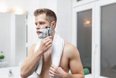 Morning hygiene, Man in the bathroom looking in mirror. Morning hygiene, Handsome man in the bathroom looking in mirror Stock Photos