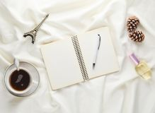 Morning inspiration and desire to trip to Paris. A cup of tea, notebook with a pen, pine cone, souvenir statue, perfume on a white. Bed sheet. Breakfast on the Royalty Free Stock Images