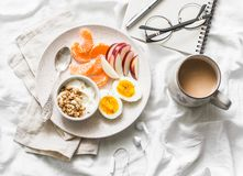 Morning inspiration and planning. Healthy breakfast - yogurt with granola, fresh fruit apples, tangerines and coffee with milk on royalty free stock image