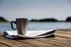 Morning at the jetty. A sunny morning at the jetty with the newspaper and a cup of coffe Royalty Free Stock Photo