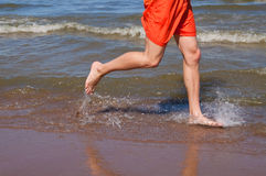 Morning jog. By bare feet on water Stock Photography
