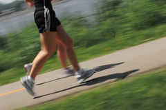 Morning Jog. Two runners run on a path next to a lake Stock Photos