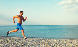 Morning jog on the beach. Man athlete running by the sea at sunset outdoors Stock Images
