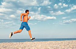 Morning jog on the beach. Man athlete runs by the sea at sunset outdoors Stock Photo