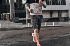 Morning jog. Close up of man in sport clothing running along the street Stock Images